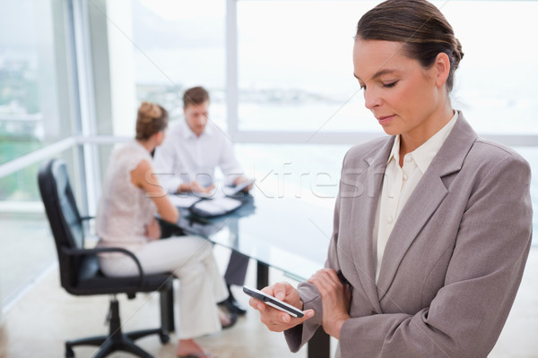 Standing real estate agent with cellphone and sitting clients behind her Stock photo © wavebreak_media