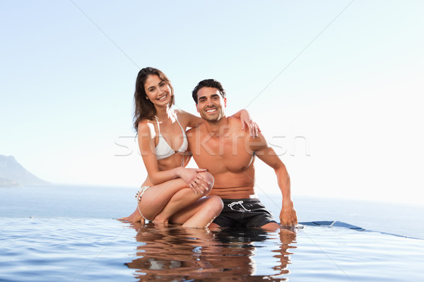 Happy couple sitting on the pool edge Stock photo © wavebreak_media