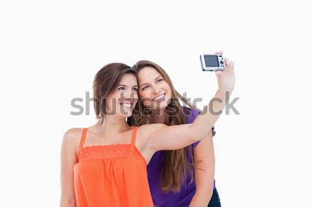 Beaming teenager taking a photo of herself and a smiling friend  Stock photo © wavebreak_media