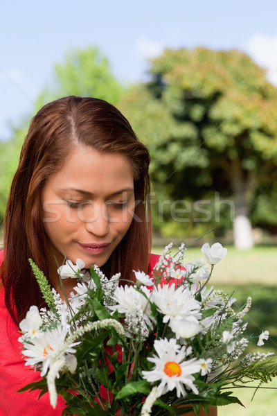 Young woman happily looking down towards a bunch of flowers while standing in an open grassland area Stock photo © wavebreak_media