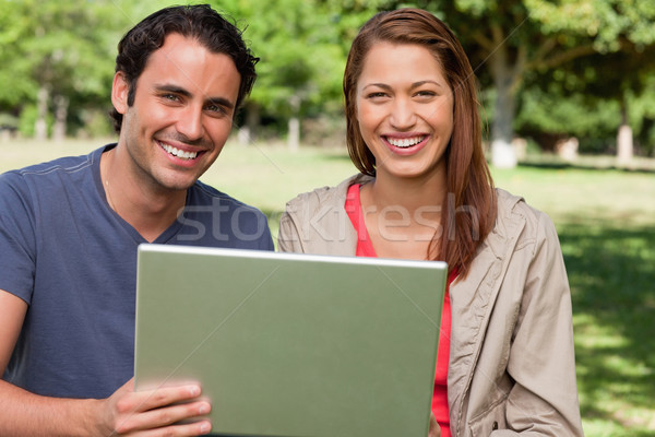 Two friends happily looking ahead as they hold a tablet in a sunny grassland Stock photo © wavebreak_media