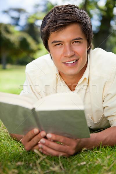 Homem olhando em linha reta à frente sorridente leitura Foto stock © wavebreak_media