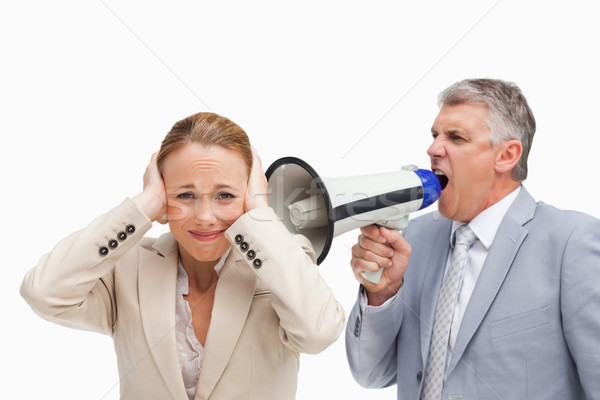 Businessman yelling with a megaphone after his colleague against white background Stock photo © wavebreak_media