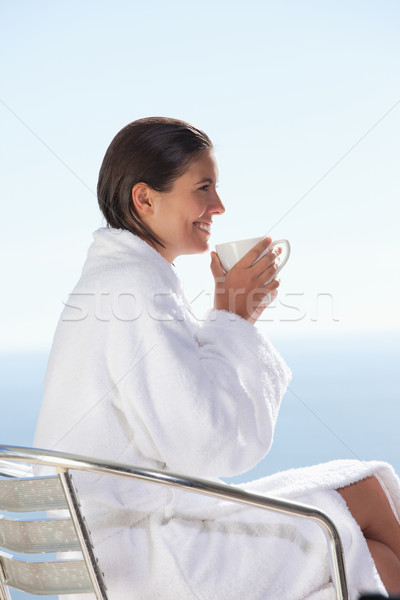Side view of smiling woman in bathrobe drinking coffee Stock photo © wavebreak_media