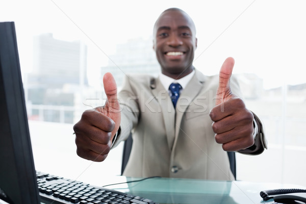 Entrepreneur working with a computer with the thumbs up in his office Stock photo © wavebreak_media