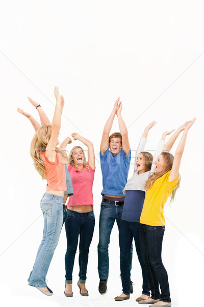 A group of friends cheering as they jump in the air and look at one another while smiling Stock photo © wavebreak_media