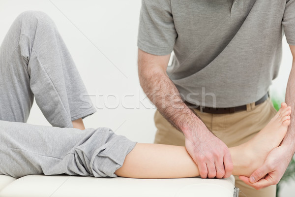 Close up on a doctor examining the foot of a woman in a bright room Stock photo © wavebreak_media
