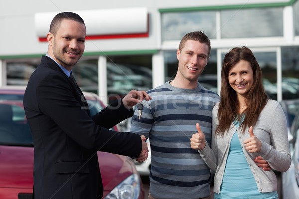 Dealer shaking hand of a man while giving him car keys in a dealership Stock photo © wavebreak_media