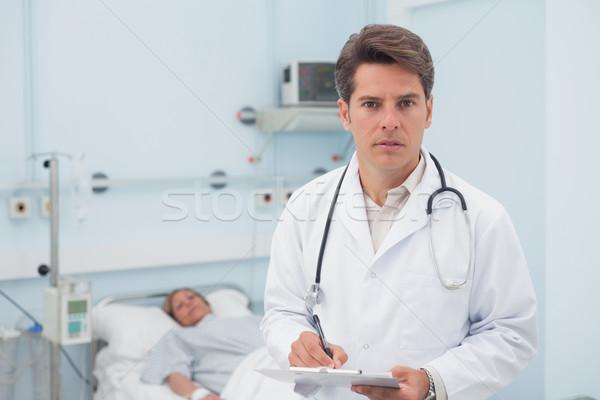 Doctor writing while holding a chart in hospital ward Stock photo © wavebreak_media