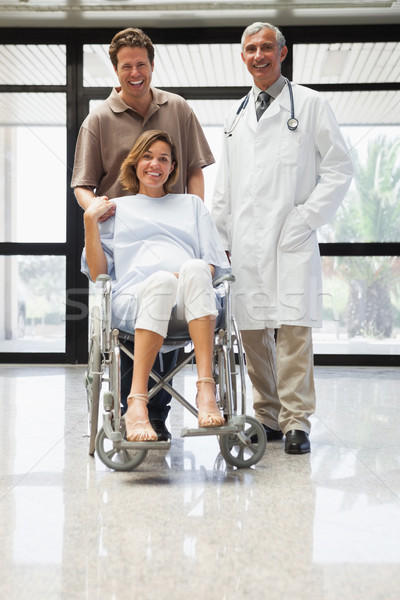 Pregnant woman in wheelchair, partner and doctor smiling in hospital corridor Stock photo © wavebreak_media