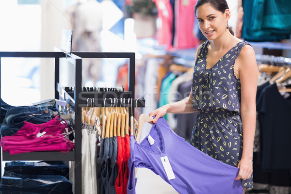 Woman holding purple shirt in clothes store and smiling Stock photo © wavebreak_media