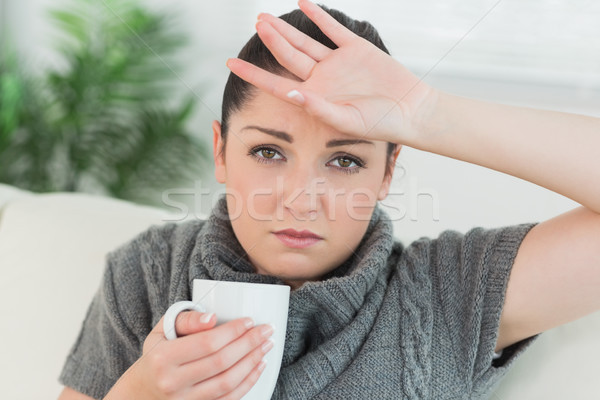 Young woman sitting on the couch in a living room while holding a cup and feeling ill Stock photo © wavebreak_media