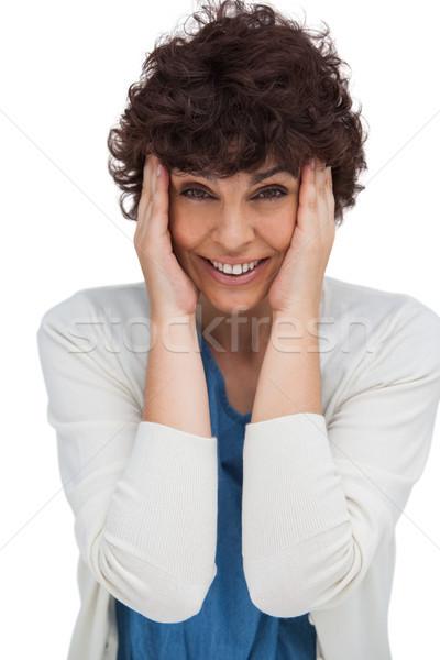 Astonished brunette woman holding her head between hands Stock photo © wavebreak_media