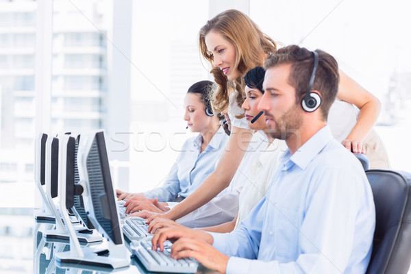 Manager and executives with headsets using computers Stock photo © wavebreak_media