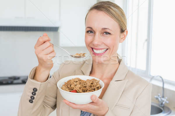 Happy businesswoman eating cereal before work in the morning Stock photo © wavebreak_media