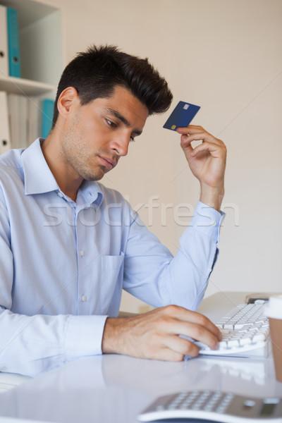 Casual businessman shopping online at his desk Stock photo © wavebreak_media