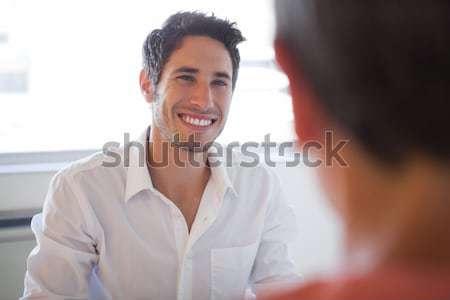 Stock fotó: Lezser · üzletemberek · beszél · asztal · mosolyog · iroda