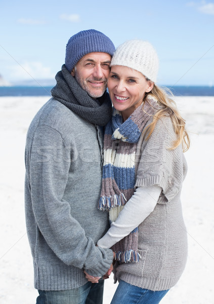 Smiling couple standing on the beach in warm clothing Stock photo © wavebreak_media