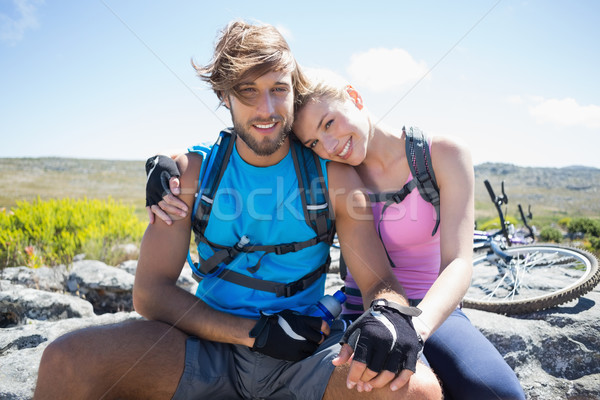 Fit cyclist couple taking a break on rocky peak smiling at camer Stock photo © wavebreak_media
