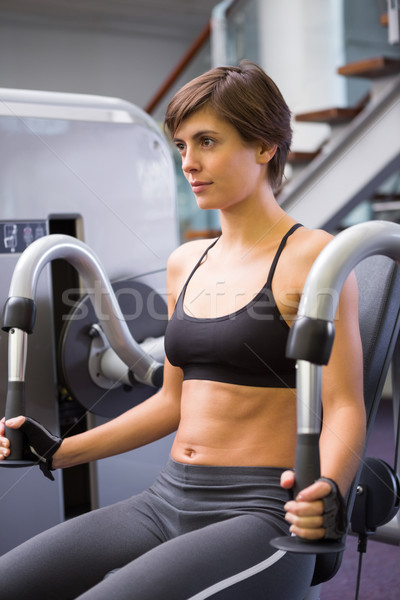 Focused brunette using weights machine for arms Stock photo © wavebreak_media