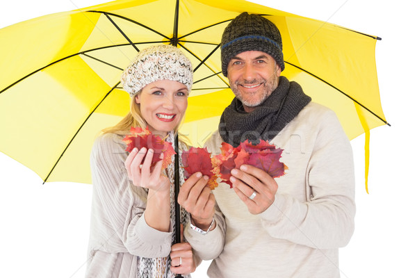 Couple in winter fashion showing autumn leaves under umbrella Stock photo © wavebreak_media