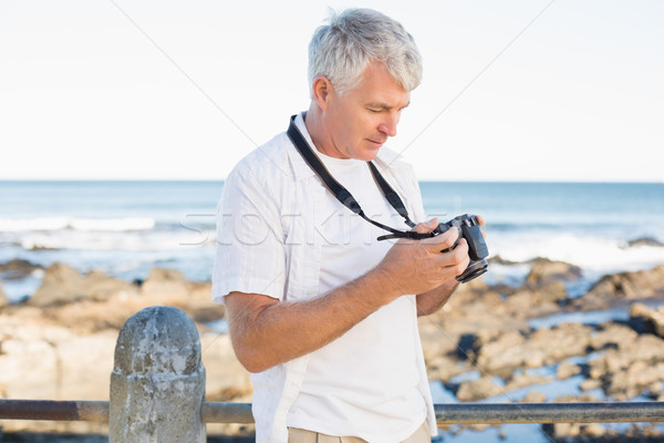 Casual mature man looking at his camera the sea Stock photo © wavebreak_media