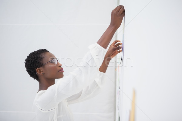 Businesswoman with glasses pinning paper up Stock photo © wavebreak_media