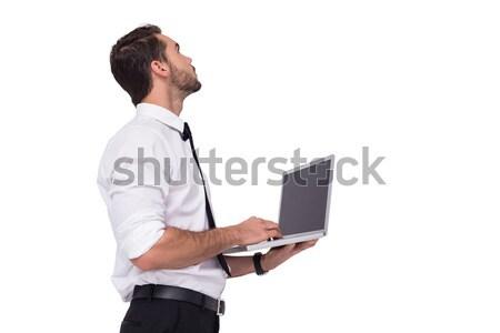 Sofisticado empresário em pé usando laptop branco negócio Foto stock © wavebreak_media