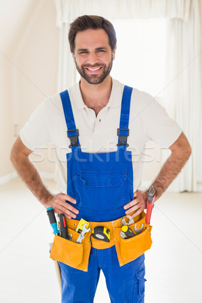 Handyman smiling at camera in tool belt Stock photo © wavebreak_media