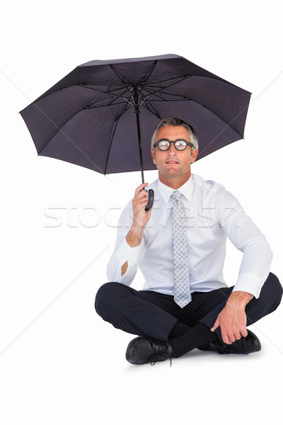 Businessman wearing glasses sheltering with umbrella Stock photo © wavebreak_media