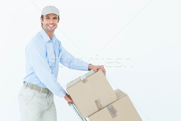 Confident delivery man pushing trolley of cardboard boxes Stock photo © wavebreak_media