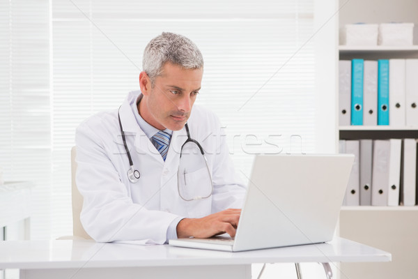 Ciddi doktor dizüstü bilgisayar kullanıyorsanız tıbbi ofis adam Stok fotoğraf © wavebreak_media