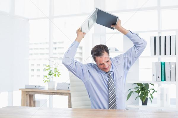 Irritated businessman trying to broke his laptop  Stock photo © wavebreak_media