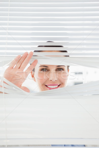 Stock photo: Woman looking out through blinds