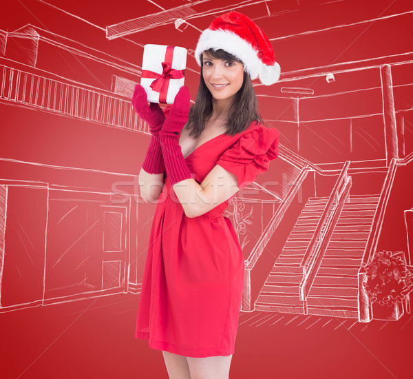 Composite image of brunette in santa hat holding a gift Stock photo © wavebreak_media