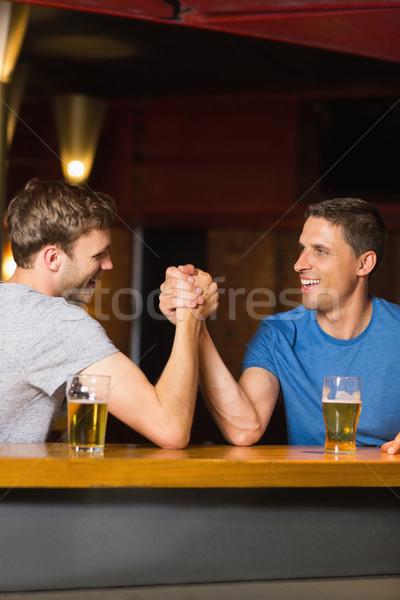 Gelukkig vriend arm worstelen ander bar man Stockfoto © wavebreak_media