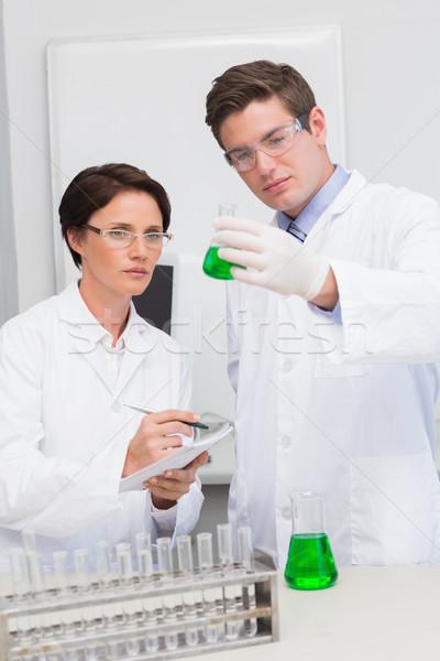 Scienziati coppa verde fluido laboratorio Foto d'archivio © wavebreak_media
