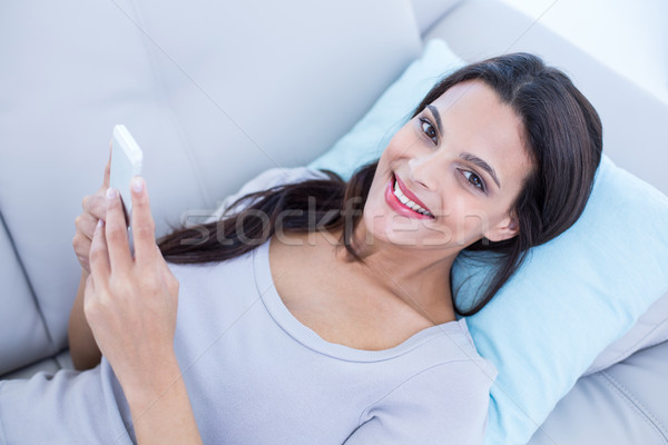 Smiling beautiful brunette relaxing on the couch and using her p Stock photo © wavebreak_media