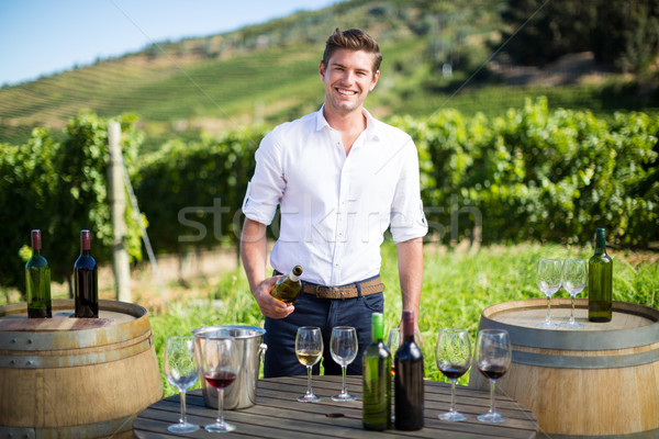 Portrait of young man holding wine bottle by table at vineyard Stock photo © wavebreak_media