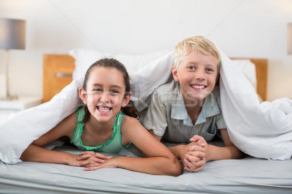 Smiling siblings lying under bed sheet in bedroom Stock photo © wavebreak_media