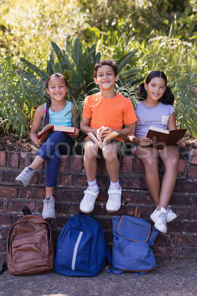 Smiling friends holding books while sitting on retaining wall Stock photo © wavebreak_media