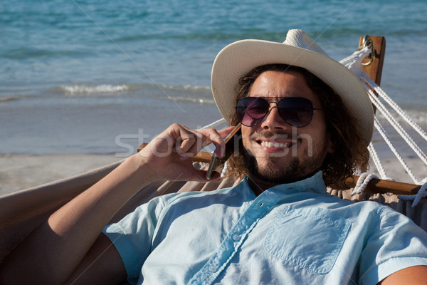 Hombre relajante hamaca hablar teléfono móvil playa Foto stock © wavebreak_media