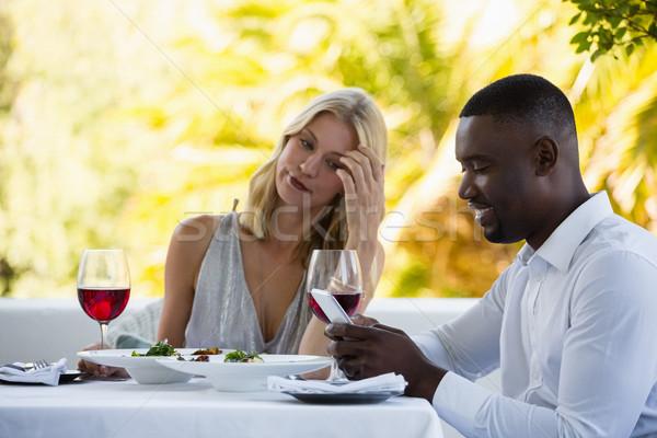 Femme regarder homme téléphone restaurant Photo stock © wavebreak_media
