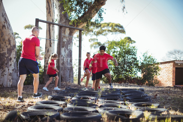 Trainer instructing kids during tyres obstacle course training Stock photo © wavebreak_media
