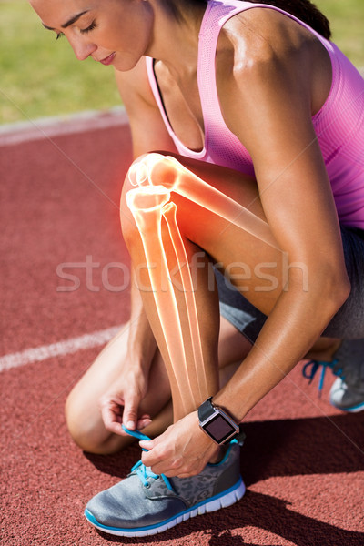 Highlighted bones of woman tying shoe lace on race track Stock photo © wavebreak_media