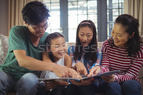 Family watching photo album together in living room Stock photo © wavebreak_media