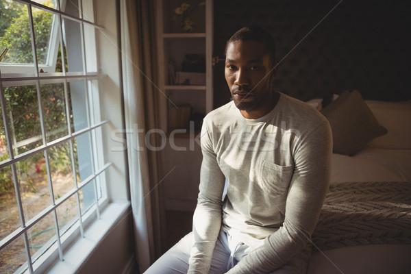 Portrait of serious man sitting on bed by window Stock photo © wavebreak_media