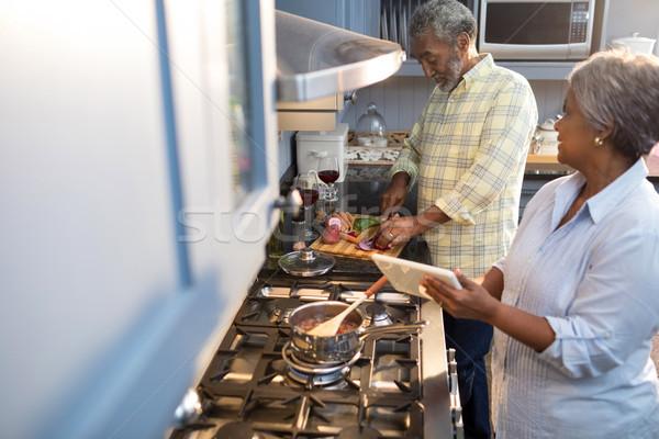 Woman showing tablet computer to man while preparing food Stock photo © wavebreak_media