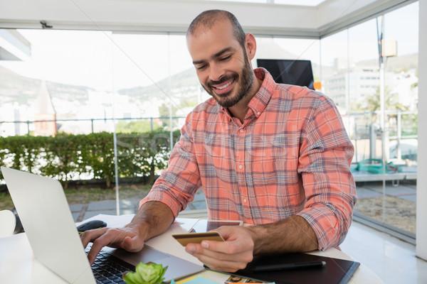улыбаясь дизайнера кредитных карт используя ноутбук столе Сток-фото © wavebreak_media