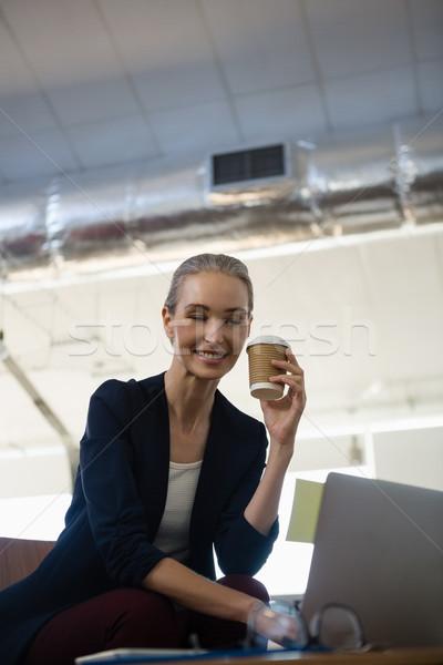 Femme d'affaires jetable tasse séance portable Photo stock © wavebreak_media